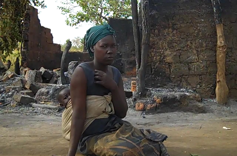 Woman sits besides her burnt hut