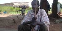 Mzee Ouma sits under a mango tree with his walking stick pondering his next move