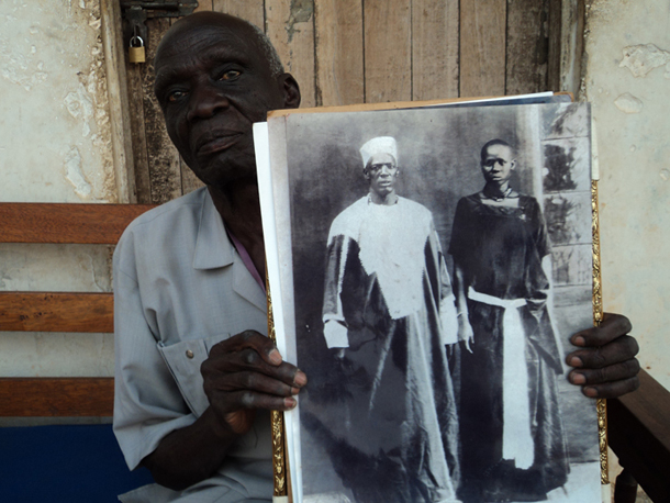 Rwot Ananians Akera of Bobi Puranga showing photo of his late father Rwot Andrea Olal Adiri
