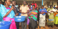 Akello Lucy and Gilbert olanya giving basins and bar of soap to mothers who give birth from Labongogali health centre