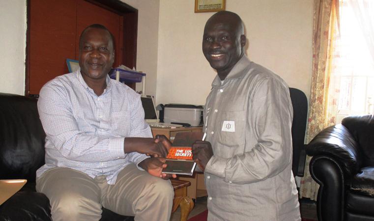Lutukumoi hands over his book to Rwot David Onen Acana