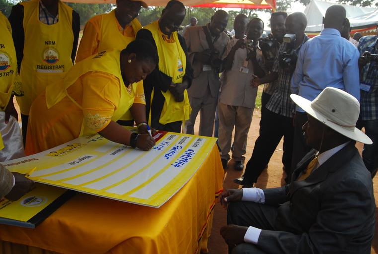 NRM Secretary General Justine Kasule Lumumba taking particulars of Mr Museveni at the launch of NRM registration