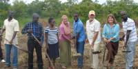 American couple, David (wearing cap) and his wife Dana Mann (with necklace) and Gulu LCV Chairman Martin Ojara Mapenduzi (wearing blue strip shirt) dig a foundation for Olee Community Primary School in Paicho Sub County on Wednesday.