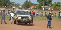 Unidentified crime preventer directs police patrol during a riot at Pece War Memorial Stadium in Gulu town in July 2015 during Secondary School Athletics Champions