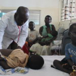 Doctor Nyeko examines a child sharing bed with another child at the ICU ward